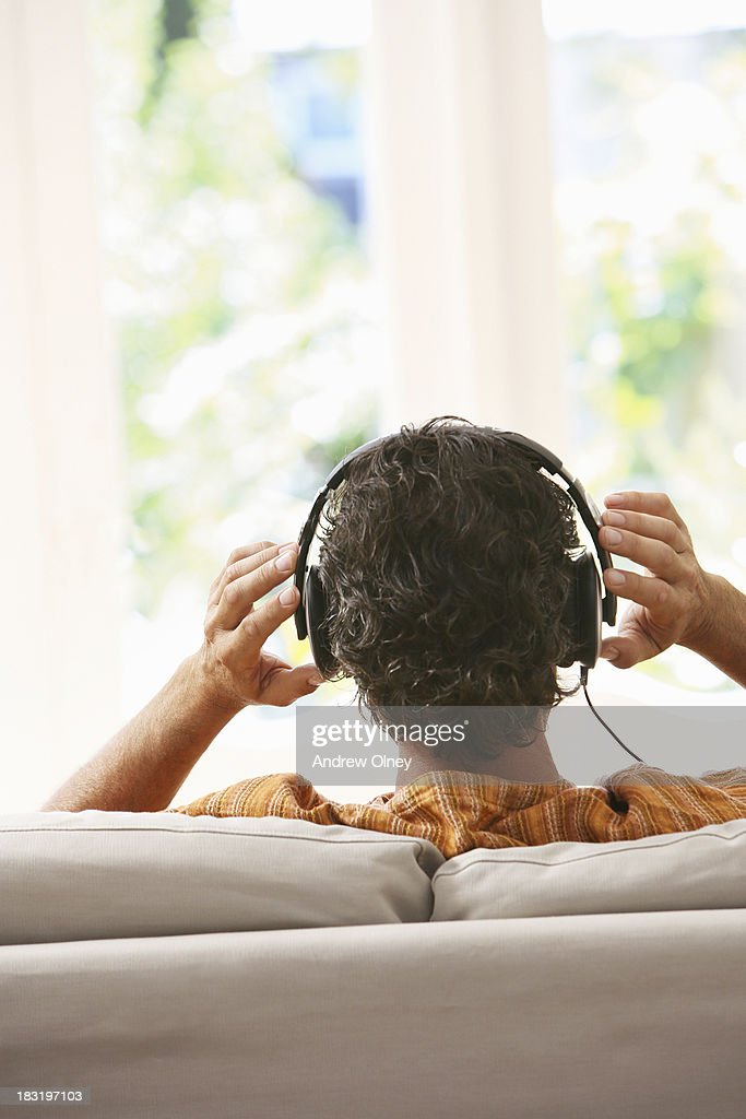 Man at home listening with headphones : Stock Photo
