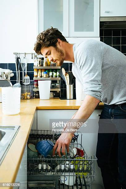 Man At Home Loading The Dishwasher