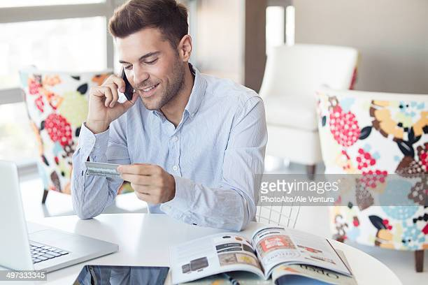 Man at home making credit card purchase over the phone