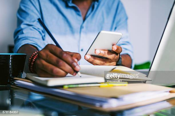 Man at home office holding smartphone making a note