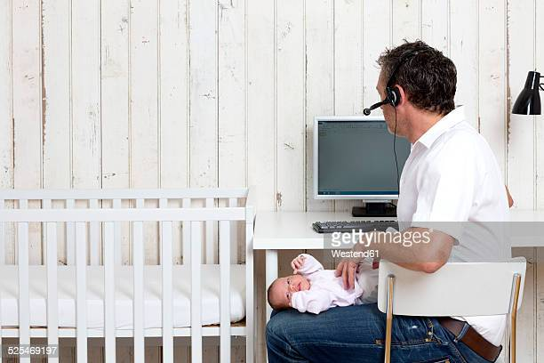 Man at home office with his baby