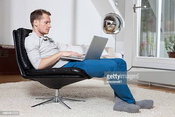 Man at home relaxing in armchair with laptop