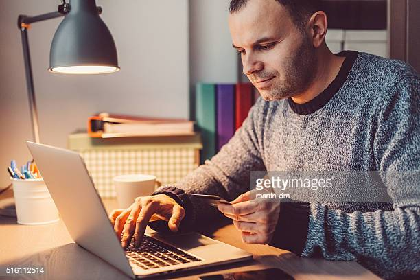 Mann zu Hause Einkaufen Online mit Kreditkarte
