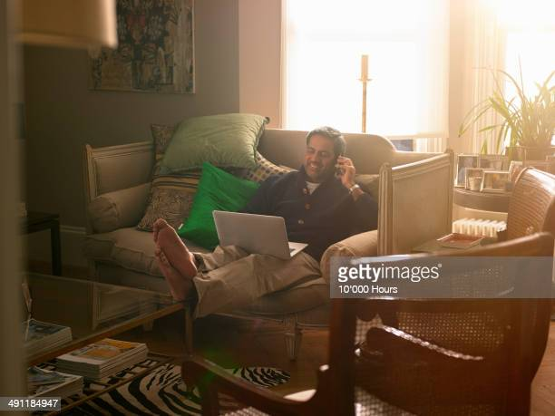 Man at home using laptop and talking on the phone