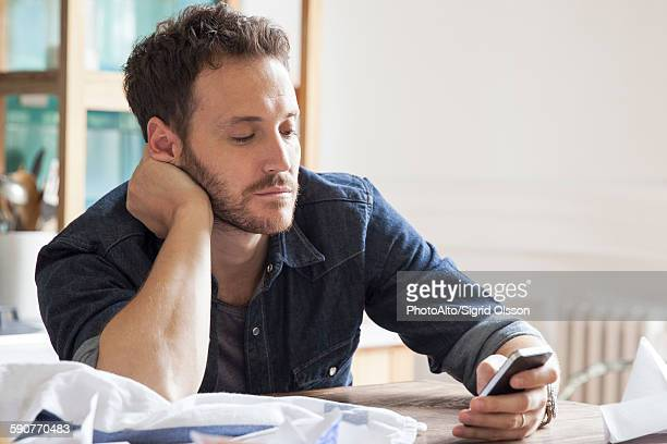 Man at home using smartphone