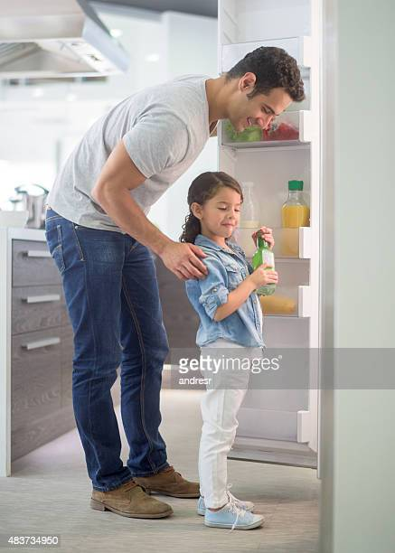 Man at home with his kid opening the fridge