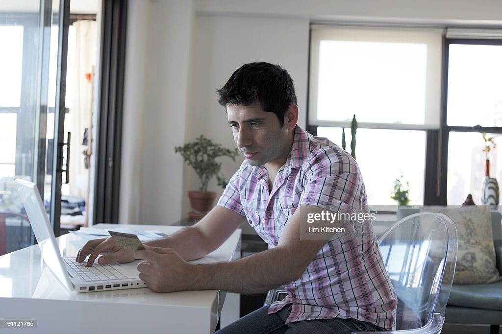 Man at laptop holding credit card : Stock Photo