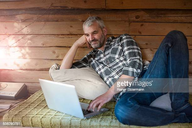Man at log cabin using computer