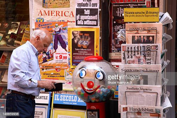 Man at news stand checking if he has enough coins for a toy.