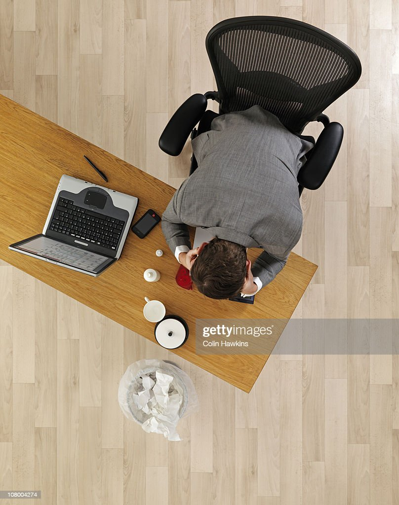 man at office desk with thought bubbles : Stock Photo