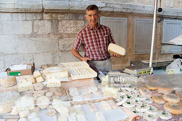 Man at sheeps cheese market stall in france