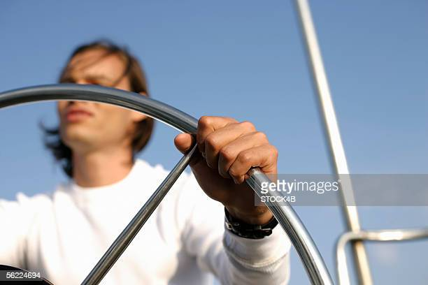 Man at steering wheel of a sailboat
