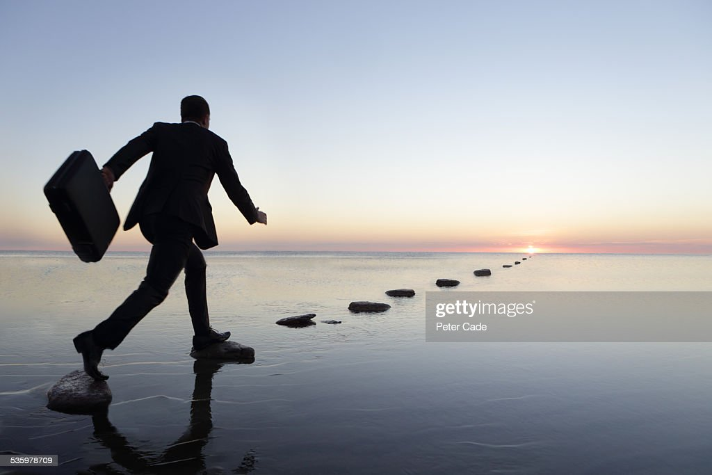 man at sunset in suit , running over steppingstone : Stock Photo
