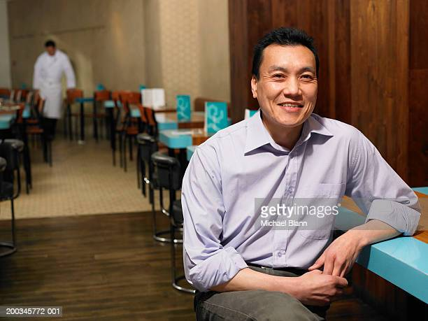 Man at table in restaurant, smiling, portrait