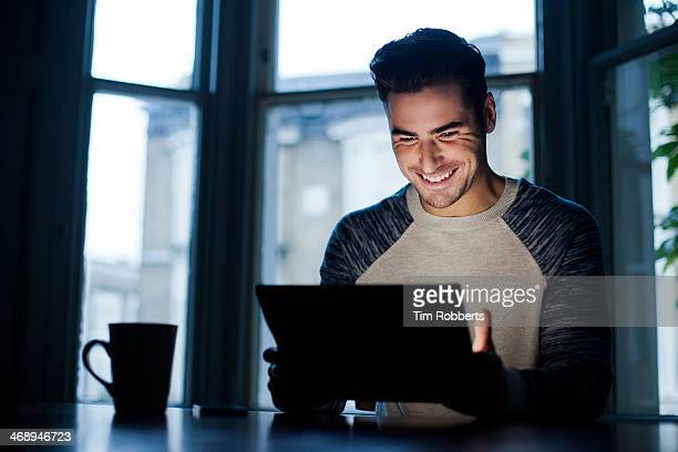 Man at table lit by digital tablet.