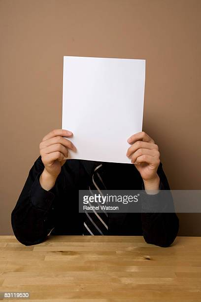 man at table with blank paper in front of face