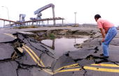 A man at Taichung Port 170km southwest of Taipei looks at a quakeopened sinkhole 25 September 1999 that is filled with molasses spilled from nearby...