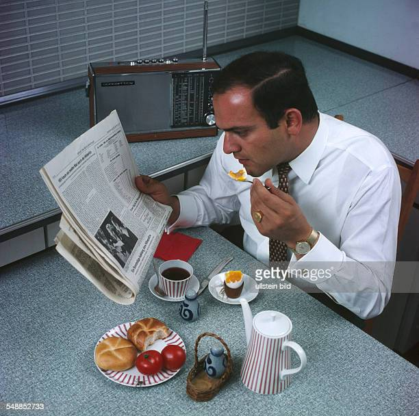 man at the braekfast table is reading the newspaper 1960s
