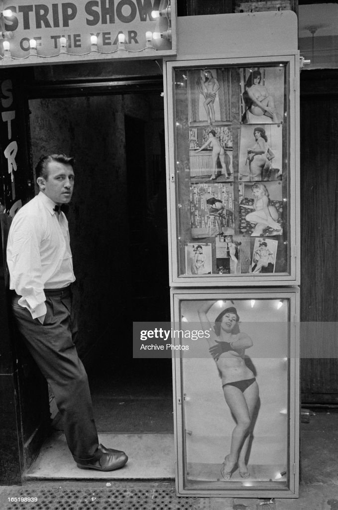 A man at the entrance to a strip club in Soho, London, April 1961.