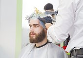 Process of a guy having his hair dyed at hairdresser.