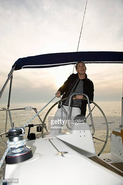 A man at the helm of a yacht adjusting the rigging