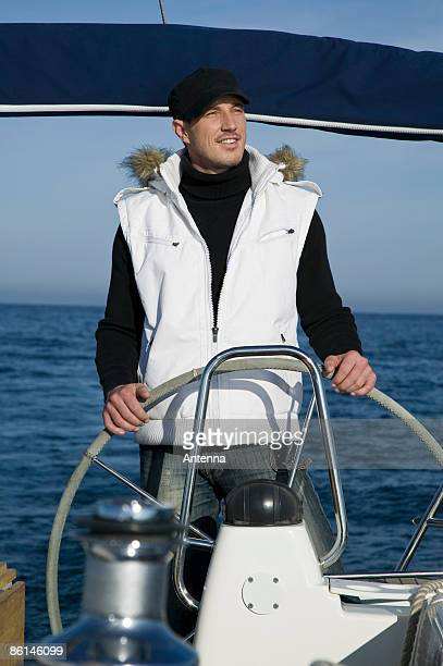 A man at the helm of a yacht