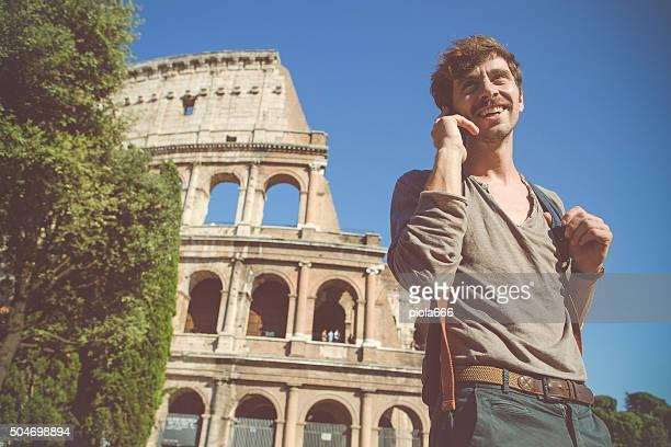 Uomo al telefono sotto il Colosseo a Roma
