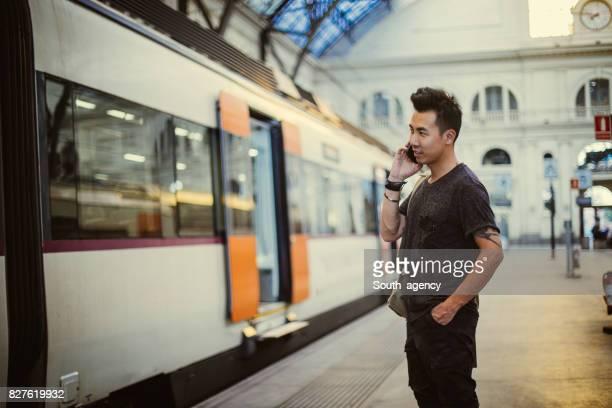 Man at train station using phone