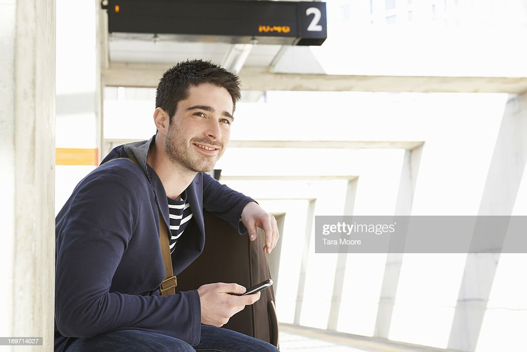 man at train station with mobile and suitcase : Stock Photo