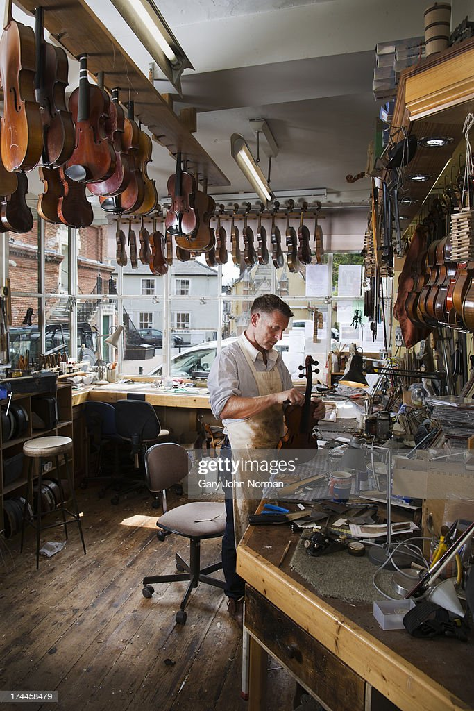 Man at work in violin shop : Stock Photo