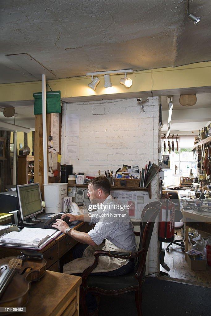 Man at work in violin shop : Stock Photo
