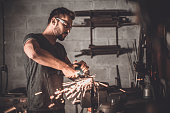 Confident young man grinding with sparks in repair shop
