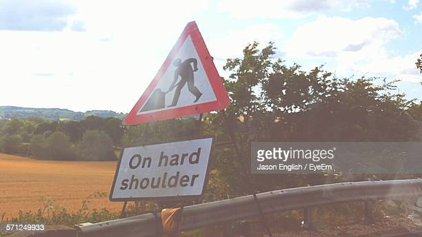 Man At Work Sign On Street By Plants Against Cloudy Sky