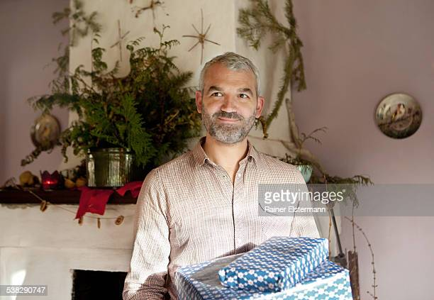 Man at X-Mas with gifts in front of chimney