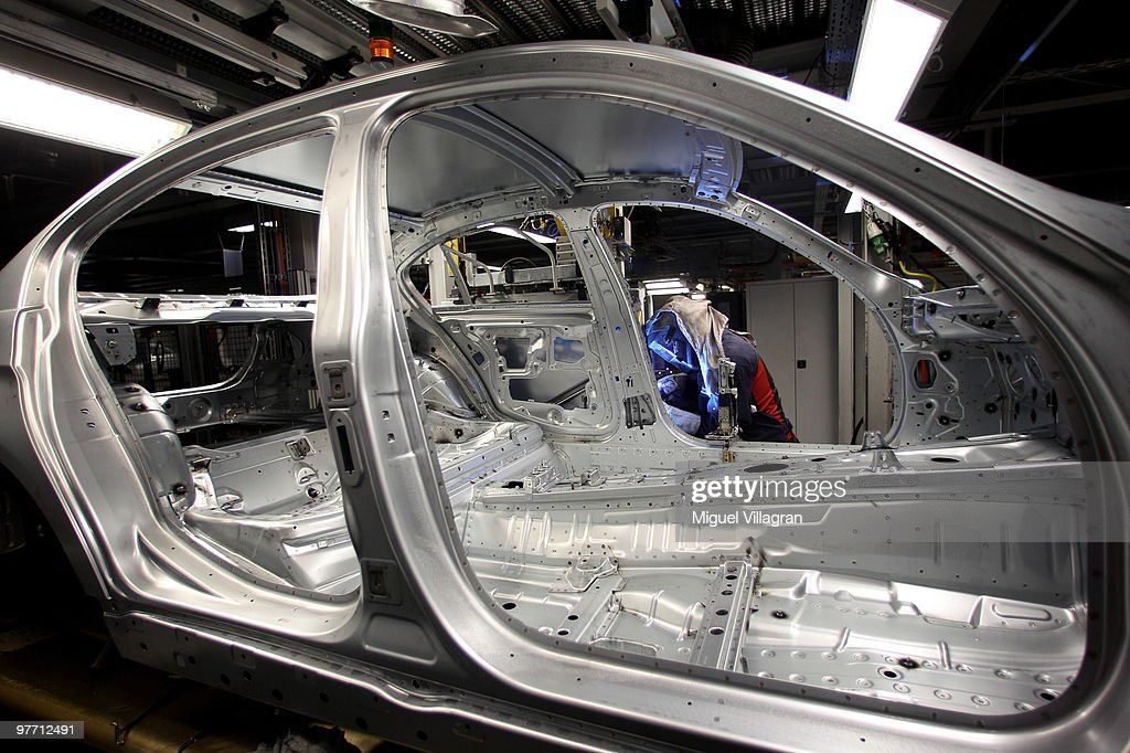 A man attaches a door to the car body on the BMW 3-series production line at the BMW factory on March 15, 2010 in Munich, Germany. The German car maker will present the company's business report for 2009 on Wednesday.
