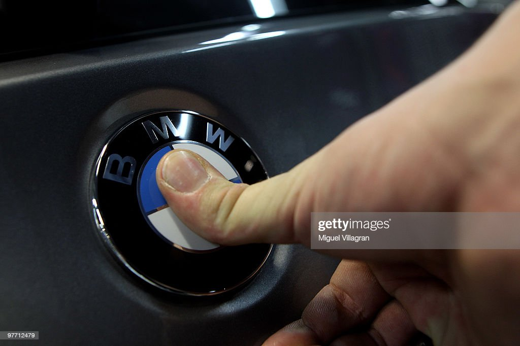 A man attaches the BMW logo onto the back of a car on the BMW 3-series production line at the BMW factory on March 15, 2010 in Munich, Germany. The German car maker will present the company's business report for 2009 on Wednesday.