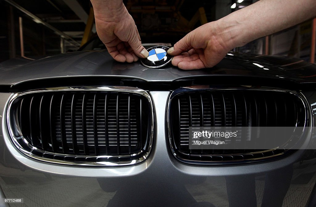 A man attaches the BMW logo onto the hood of a car on the BMW 3-series production line at the BMW factory on March 15, 2010 in Munich, Germany. The German car maker will present the company's business report for 2009 on Wednesday.