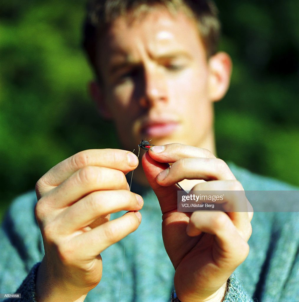 Man attaching fly to fishing hook, close up : Stock Photo