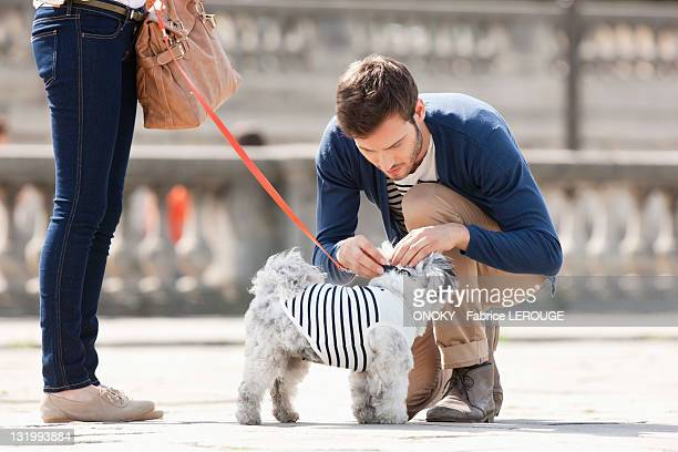 Man attaching leash on a puppy, Paris, Ile-de-France, France