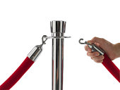 Man attaching velvet rope to barrier pole, close-up of hand