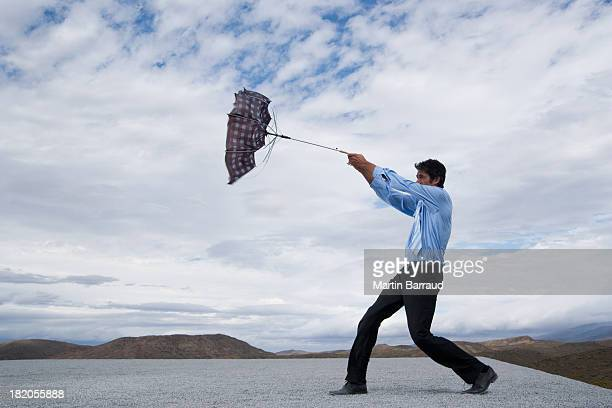 Man attempting to control umbrella in the wind