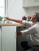 Man attempting to fix sink in kitchen