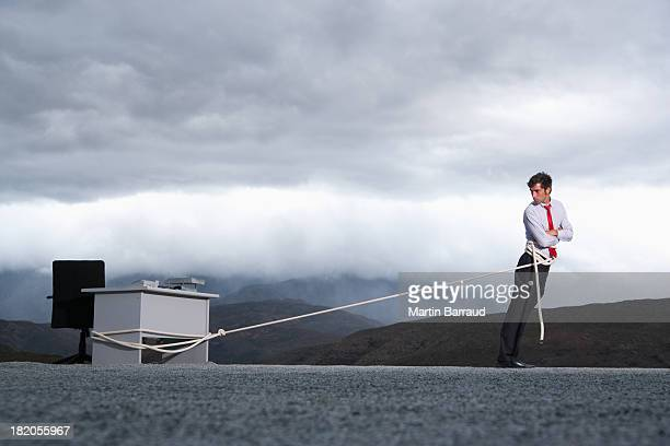 Man attempting to pull his desk outdoors with a long rope