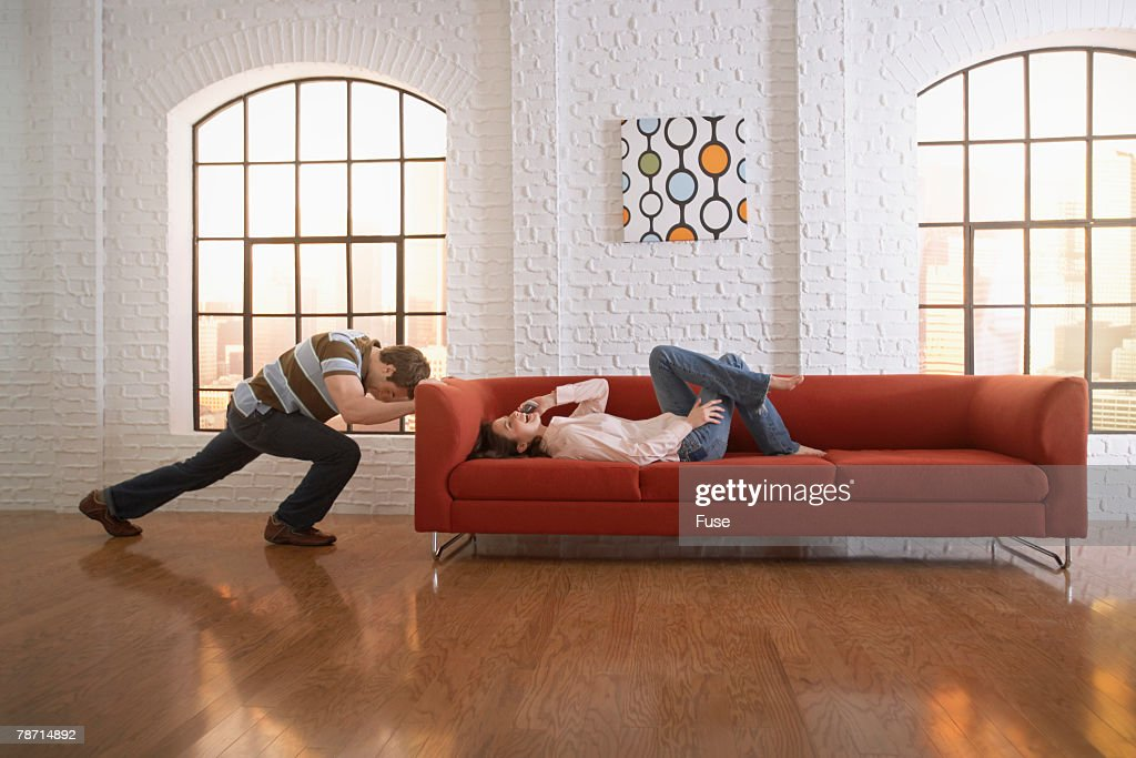 Man Attempting to Push His Sofa