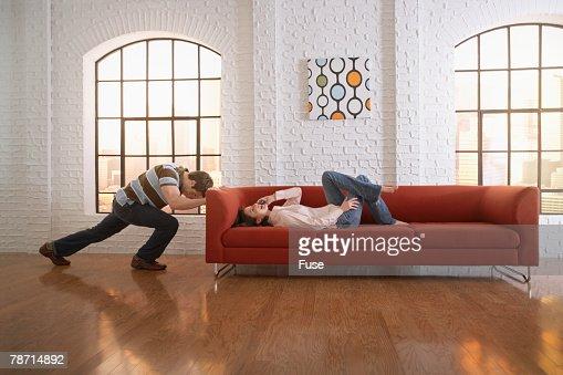 Man Attempting to Push His Sofa