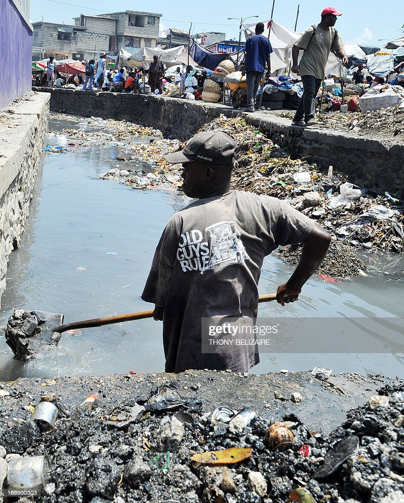 A man attempts to clean garbage out of a canal on May 17, 2013 in Martissant, a suburb of Port-au-Prince. AFP PHOTO Thony BELIZAIRE