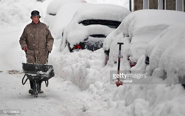 A man attempts to clear snow around cars on November 30 2010 in Dunning Scotland United Kingdom Freezing weather conditions and snow that has created...