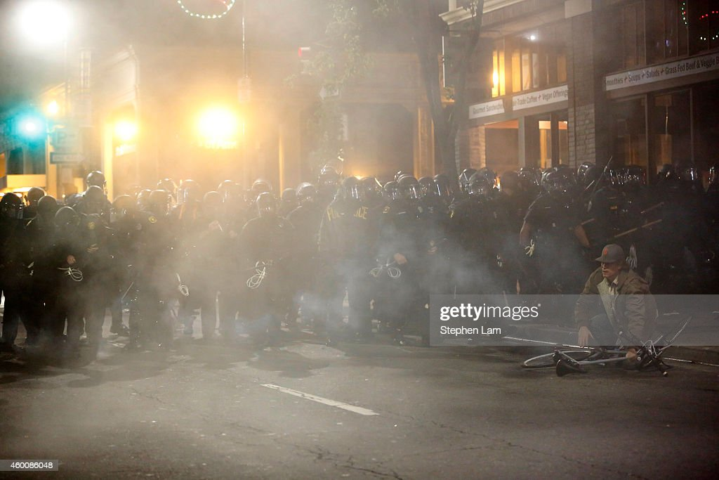 A man attempts to pick up his bicycle amidst a cloud of teargas during the fourth night of demonstrations over recent grand jury decisions in...