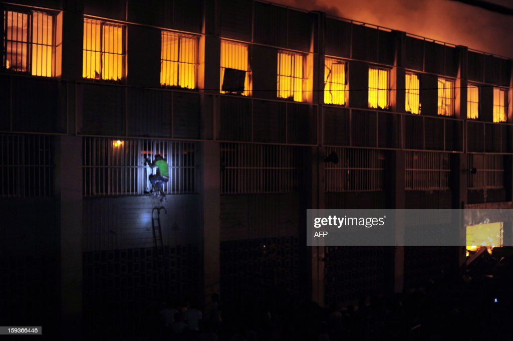 A man attempts to retrieve some belongings by breaking through a window of the burning Lome's Grand Marche, (''Lome Big Market'') late on January 11, 2013 in Lome. Crowds of people filled the streets surrounding the multi-storey structure, as a few vendors entered the burning building to save their goods. AFP Photo / Daniel Hayduk