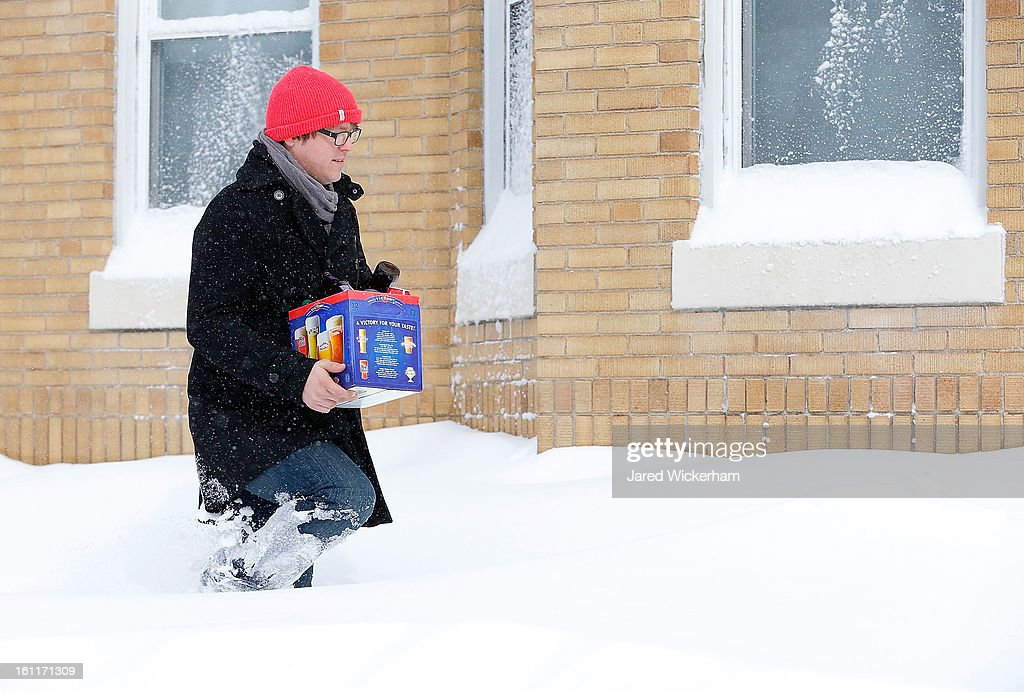 A man attempts to walk through the snow covered sidewalk with a case of beer on February 9, 2013 in Boston, Massachusetts. The powerful storm has knocked out power to 650,000 and dumped more than two feet of snow in parts of New England.